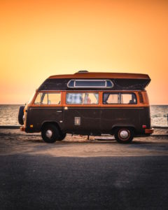 Campervan parked in front of a beach sunset
